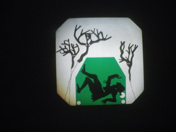 shadow puppets of thre tree creatures trapping a person in a green box with breathign holes