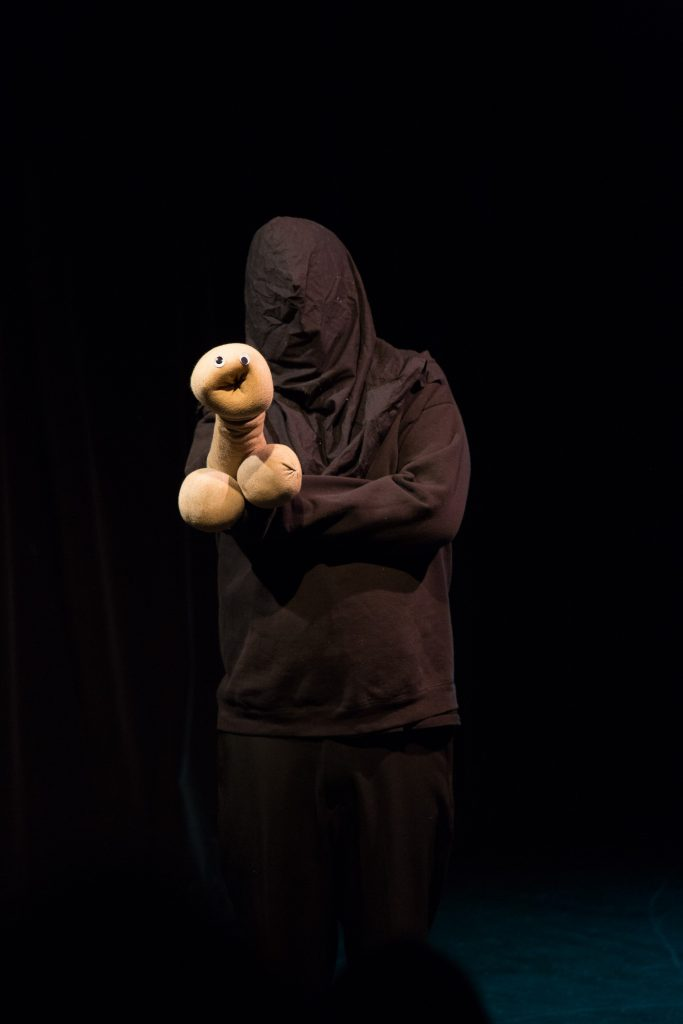a puppet and performer in black box